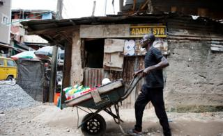 A man pushes a wheelbarrow through a street at Okepopo district in Lagos