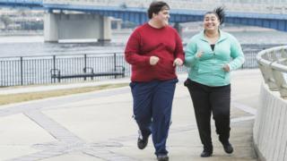 Полные девушка и молодой человек на пробежке в городе
