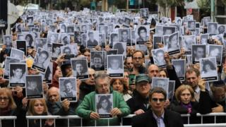 Picture released by Noticias Argentinas showing people holding pictures of victims of the 1994 bombing attack against the Argentine Israelite Mutual Association (AMIA) Jewish community center that killed 85 people and injured 300, during the commemoration of the attack's 25th anniversary, in Buenos Aires on July 18, 2019.