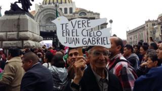 """Hombre sostiene un cartel que dice """"te veré en el cielo Juan Gabriel""""."""
