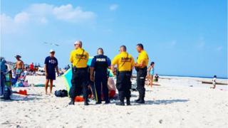 Police on beach surrounding injured woman