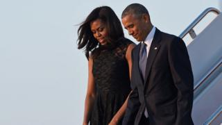 Barack and Michelle Obama walk down the steps of Air Force One