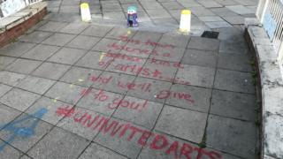 The repainted bollards and graffiti on pavement