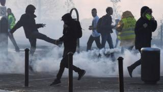 French protesters run through tear gas in Quimper