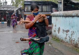 A woman carries her son as she tries to protect him from heavy rain