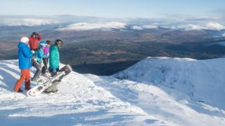 Skiers and snowboards looking down Winger Wall at Nevis Range