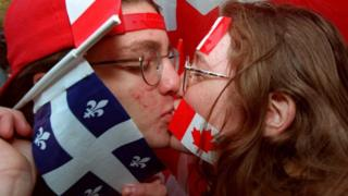 Dos manifestantes se besan portando las banderas de Quebec y Canadá. (Foto: Andre Pichette/AFP/Getty)