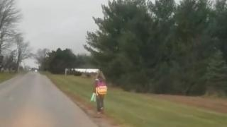 10 year old walking on road with backpack