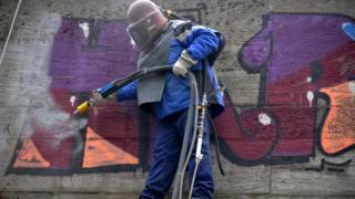 A worker removes a graffiti with a sandblaster from a wall on April 4, 2013 in Munich, southern Germany.