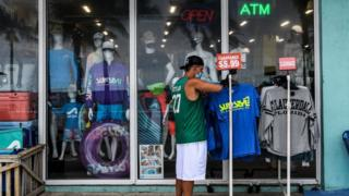 A man wears a mask as he browses through shirts for sale on Fort Lauderdale beachfront