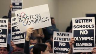 People hold up placards against the Olympic Games coming to Boston, during the first public forum regarding the city's 2024 Olympic bid, in Boston. 5 February 2015
