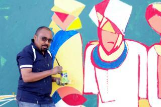 رجل يقف قرب جدارية ممسكا بفرشاة رسم