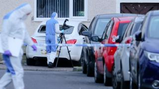 Police forensic officers at the scene of the shooting
