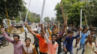 Members of India's low-caste Dalit community sticks and shout slogans in Ahmedabad, India, Wednesday, July 20, 2016.