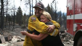 Kathy Besk (R) hugs CalFire firefighter Tommy Janow (L) after he found three of her rings in the burned-out ruins of her home