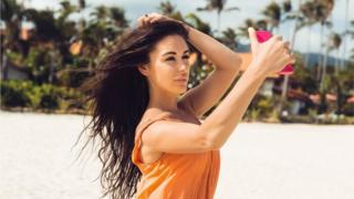 Imagem de uma mulher tirando uma selfie na praia, em pose sensual