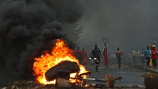 Protestors opposed to the Burundian president Pierre Nkurunziza's third term in office gather by a burning barricade during a demonstration in the Cibitoke neighbourhood of Bujumbura on May 19, 2015.