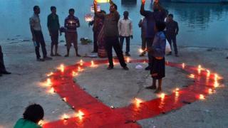 人们在世界艾滋病日当天点燃蜡烛