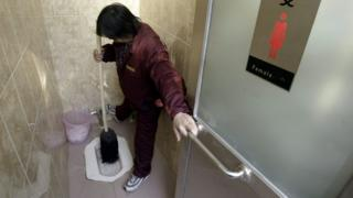 A file photo of a worker cleaning a squat toilet in China