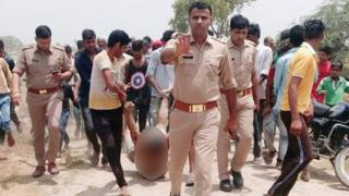 A picture of a victim of lynching being dragged in front of a group of policemen.