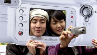 People posing with giant cardboard Kodak camera