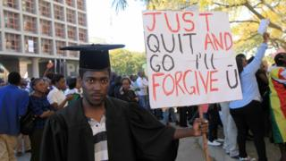 """A protesters in Harare, Zimbabwe, dressed in a graduation gown and cap holding a sign reading """"Just Quit And Go I'll Fogive U"""" - Wednesday 3 August 2016"""