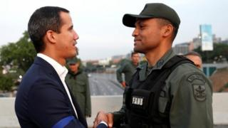 "Venezuelan opposition leader Juan Guaido, who many nations have recognised as the country""s rightful interim ruler, shakes hands with a military member near the Generalisimo Francisco de Miranda Airbase ""La Carlota"", in Caracas, Venezuela April 30, 2019."