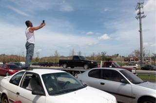 Un hombre se sube en su coche buscando señal para el celular.