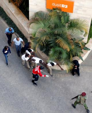 Aerial high angle shot people are evacuated at the scene where explosions and gunshots were heard at the Dusit hotel compound, in Nairobi