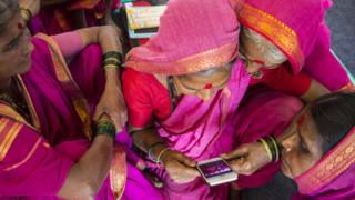 women checking a mobile phone together