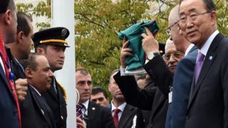 Mahmoud Abbas raises a folded Palestinian flag at UN headquarters in New York (30 September 2015)