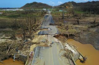 A man cycles on a destroyed road in Toa Alta, Puerto Rico.