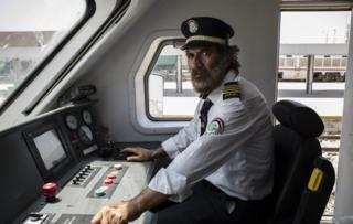 Ali Al-Karkhi, Senior Train Driving Inspector sits in the train's cockpit