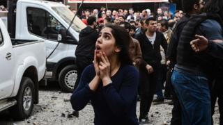 A woman reacts as she looks at the site of a strong blast near the riot police headquarters in the centre of Diyarbakir, south-eastern Turkey, on 11 April 2017