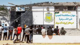 Migrants stand outside a detention centre used by the Libyan Government in the capital Tripoli