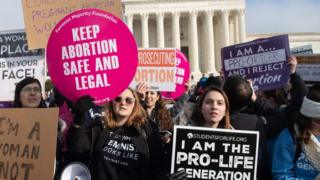 """Pro-choice activists hold signs alongside anti-abortion activists participating in the """"March for Life,"""" an annual event to mark the anniversary of the 1973 Supreme Court case Roe v. Wade, which legalized abortion in the US, outside the US Supreme Court in Washington, DC"""