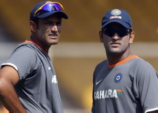 Indian cricketers Anil Kumble (L) and Mahendra Singh Dhoni watch teammates during a training session ahead of the second Test match between India and South Africa in Ahmedabad on April 2, 2008.