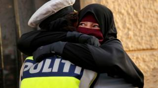 Danish police officer hugs a woman wearing a niqab