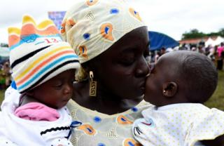 A mother kisses one of her twins during the Igbo-Ora World Twins festival.