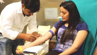 रक्तदान करती युवती