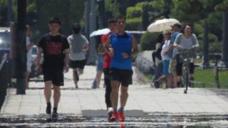 The effects of heat haze is seen in this photograph as pedestrians walk along a street during a heatwave in Tokyo on August 2