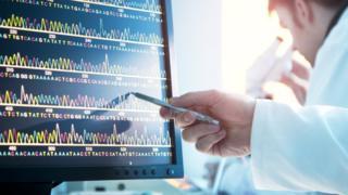 Médico analiza secuencia de ADN frente a computador.