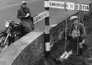 Boys swing from road sign