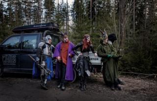 A group of live action role players lean against a van.