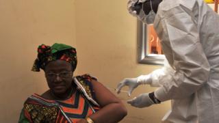 Mujer recibiendo una inyección contra el Ébola.