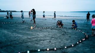 People on a beach next to a heart made of candles