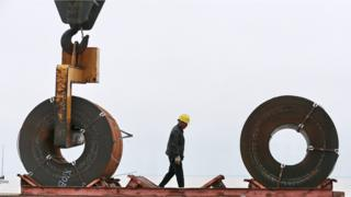 This photo taken on May 19, 2018 shows a worker preparing to lift a roll of steel with a crane at a shipyard in Nantong in China's eastern Jiangsu province.