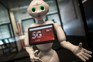 Pepper robot with screen advertising 5G logo