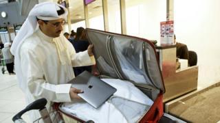Diz üstü bilgisayarını bavuluna yerleştiren Kuveytli bir yolcu.