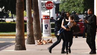 Mujer con chico en brazos y agentes de policía detrás